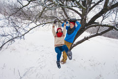 Guy and girl walk and have fun in the forest. In winter Royalty Free Stock Photo