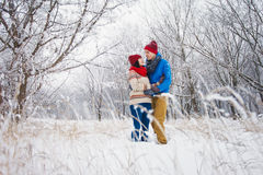Guy and girl walk and have fun in the forest. In winter Royalty Free Stock Photos