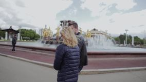 A guy and a girl are walking along a beautiful park and chatting vividly. stock footage