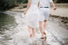 the guy and the girl are walking along the seashore royalty free stock image
