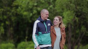 Guy with a girl walking through the park. They embrace. They talk and laugh. stock footage