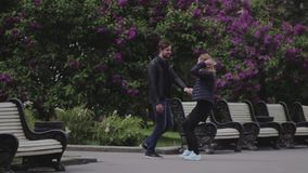 A guy and a girl are walking in the park zone holding hands. Lovers. A park. City. Fountains. Love stock video