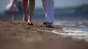 Guy and girl are walking on the sand stock video