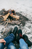 Guy and girl warm feet near a fire. Cold winter on the street Stock Images