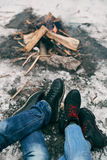 Guy and girl warm feet near a fire. Cold winter on the street Stock Photography