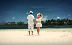 A guy and a girl in white clothes on the shore of the island. Maldives. White sand. Guraidhoo. Royalty Free Stock Photography