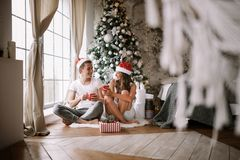 Guy and girl in white t-shirts and Santa Claus hats sit with red cups on the floor in front of the window next to the stock images