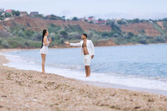 Guy and girl in white talking at waters edge Stock Images