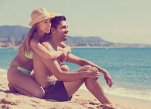 Guy and girlfriend resting on sandy beach. Happy guy and smiling girlfriend resting on sandy beach at vacation together stock photo