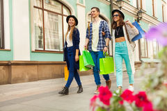 Guy and girls with shopping bags during travel Royalty Free Stock Photo