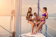 Guy with girls on yacht. People sit on yacht railing. Summer trip with friends. What a beautiful day Stock Images