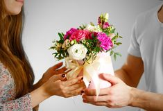 The guy gives a bouquet of flowers to a girl. Composition of flo. Wers in a pink hatbox. Tied with wide white ribbon and bow Stock Photography