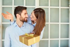 The guy gives a gift box to his girlfriend. Young couple on holiday. St. Valentine`s Day stock photo