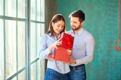 The guy gives a gift box to his girlfriend. royalty free stock photo