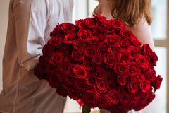 The guy gives the girl a big bouquet of roses stock image