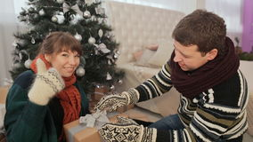 The guy gives the girl Christmas gifts. The girl model shows off a gift to the viewer and also shows the sign of the stock footage