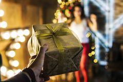 Guy gives his girlfriend a gift for Christmas or new year. Box in Golden foil closeup on a background of jubilant happiness women stock photography