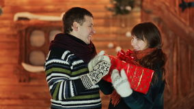 The guy gives his girlfriend a red Christmas present against the backdrop of a fairy-tale house. The girl is very happy. Christmas and New Year theme stock video footage