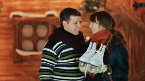 A guy gives his white skates to his girlfriend, which she is very happy about against the background of a magical fairy. Tale house. Christmas and New Year stock footage