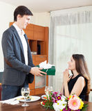 Guy giving a gift to a girl for a romantic dinner Stock Photos