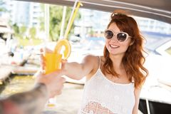 Beautiful girl is going to drink cocktail with men on yacht stock images