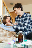 Guy giving  medicament to unwell wife Royalty Free Stock Image