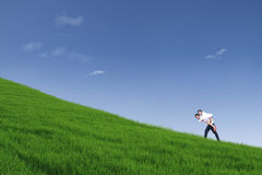 Guy giving piggyback ride on hill under blue sky Stock Photos
