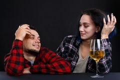 A guy with a girl relaxed with alcohol at a bar counter on a black background Royalty Free Stock Photos