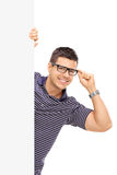 Guy with glasses posing behind blank panel Royalty Free Stock Photography