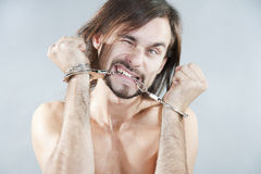 Guy gnaws his handcuffs Stock Photo