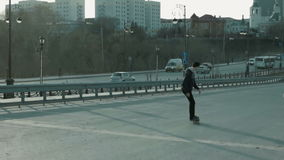 The guy goes on a skateboard on a slope near the motorway. In the city stock video