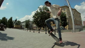Guy goes on a skateboard on the street and doing tricks stock video footage