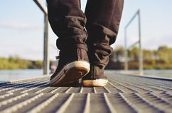 Guy goes in sneakers the pier Royalty Free Stock Photos