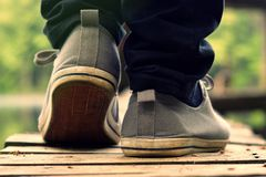 Guy goes in sneakers on the pier Royalty Free Stock Images