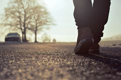 Guy goes in sneakers on the street at sunrise. Guy goes in sneakers on the street at misty sunrise Stock Image
