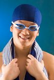 Guy in goggles. Portrait of happy sportsman in swimming cap and goggles over blue background Royalty Free Stock Photography