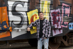 Guy by graffiti covered train Stock Photography