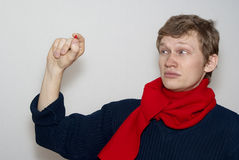 Guy on a gray background is considering pill. The guy sees a pill in a red scarf Royalty Free Stock Photos