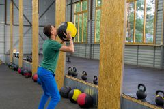 Guy in a green T-shirt and blue pants trains in the gym, throws royalty free stock image