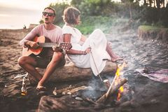 Guy with guitar and his girlfriend sitting on log and singing for his friends on summer evening by campfire Stock Images