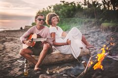 Guy with guitar and his girlfriend sitting on log and singing for his friends on summer evening by campfire Royalty Free Stock Image