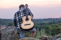 Guy with guitar play songs at sunny nature. Young guy with guitar outdoors at sunset, music and travel concept Stock Images