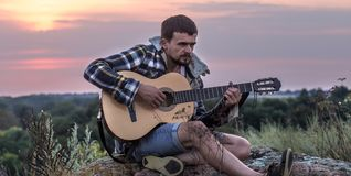 Guy with guitar play songs at sunny nature. Young guy with guitar outdoors at sunset, music and travel concept royalty free stock photography
