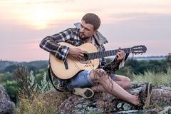 Guy with guitar play songs at sunny nature. Young guy with guitar outdoors at sunset, music and travel concept Stock Photos