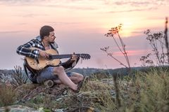 Guy with guitar play songs at sunny nature. Young guy with guitar outdoors at sunset, music and travel concept Royalty Free Stock Images