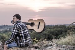Guy with guitar play songs at sunny nature. Young guy with guitar outdoors at sunset, music and travel concept Royalty Free Stock Image