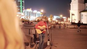 A guy with a guitar playing in the town square at night Visible city lights. stock video footage