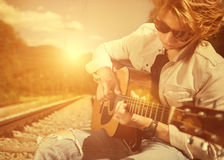 Guy with guitar on the railway Stock Photo