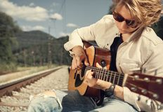 Guy with guitar on the railway Stock Images