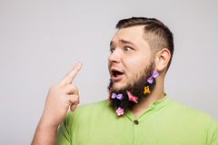 Guy with hair clips. Portrait of a young man with colorful hair clips on his beard showing middle finger gesturing fuck isolated on white background Stock Photo